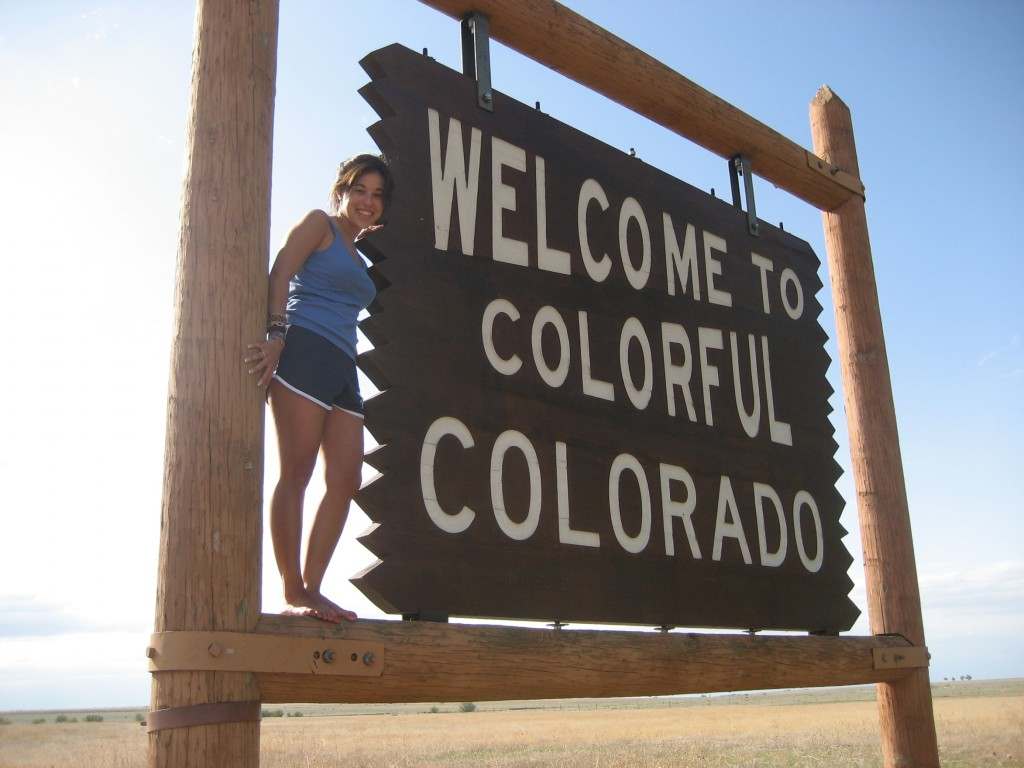 Girl standing on colorful Colorado sign