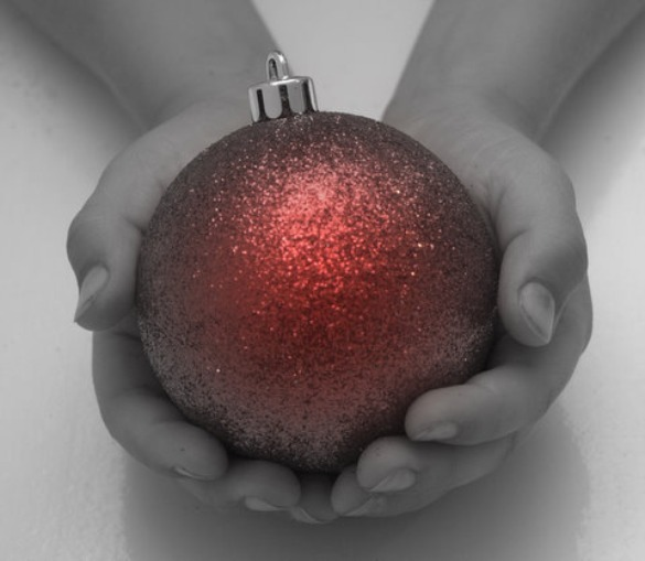 Hands holding red globe ornament