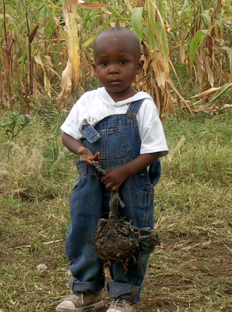Tanzanian boy in overalls holding trash ball