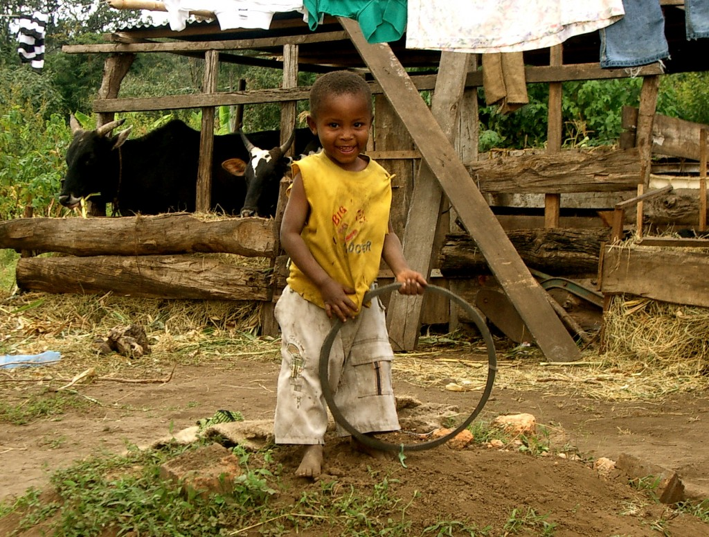 Tanzanian boy smiling and holding tire rim toy
