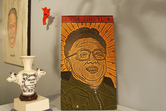 Painting of Kim Jong Il in red, yellow, and green.