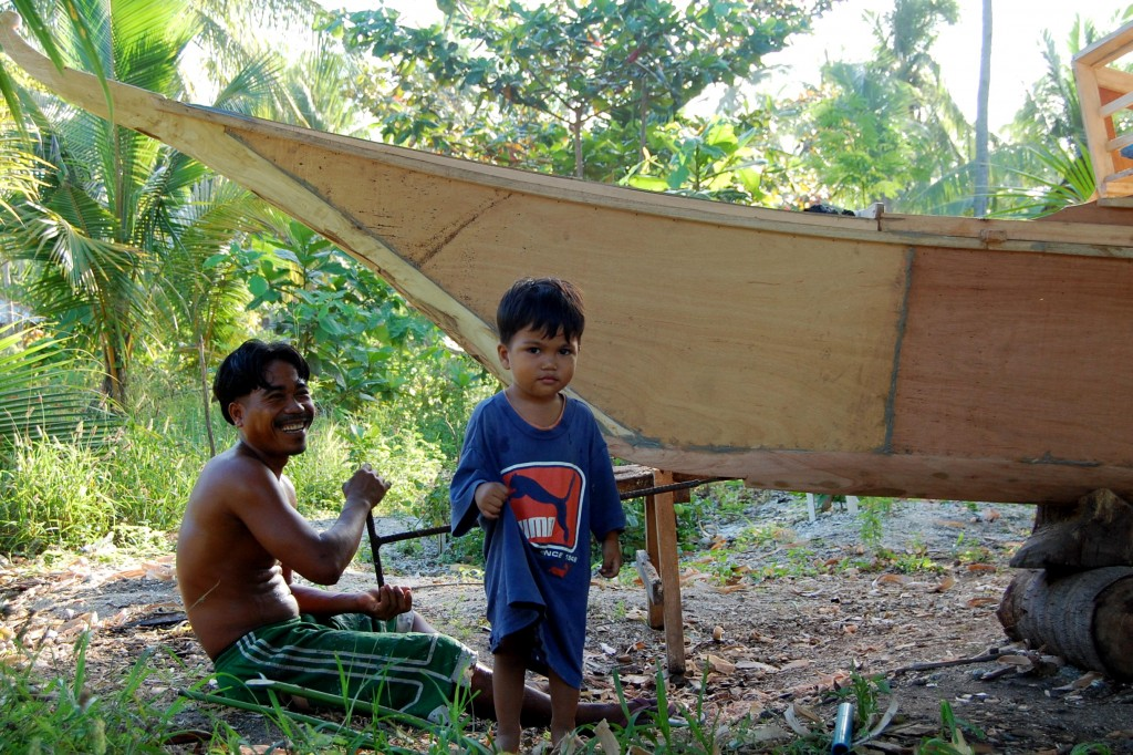 Filipino dad building boat with son