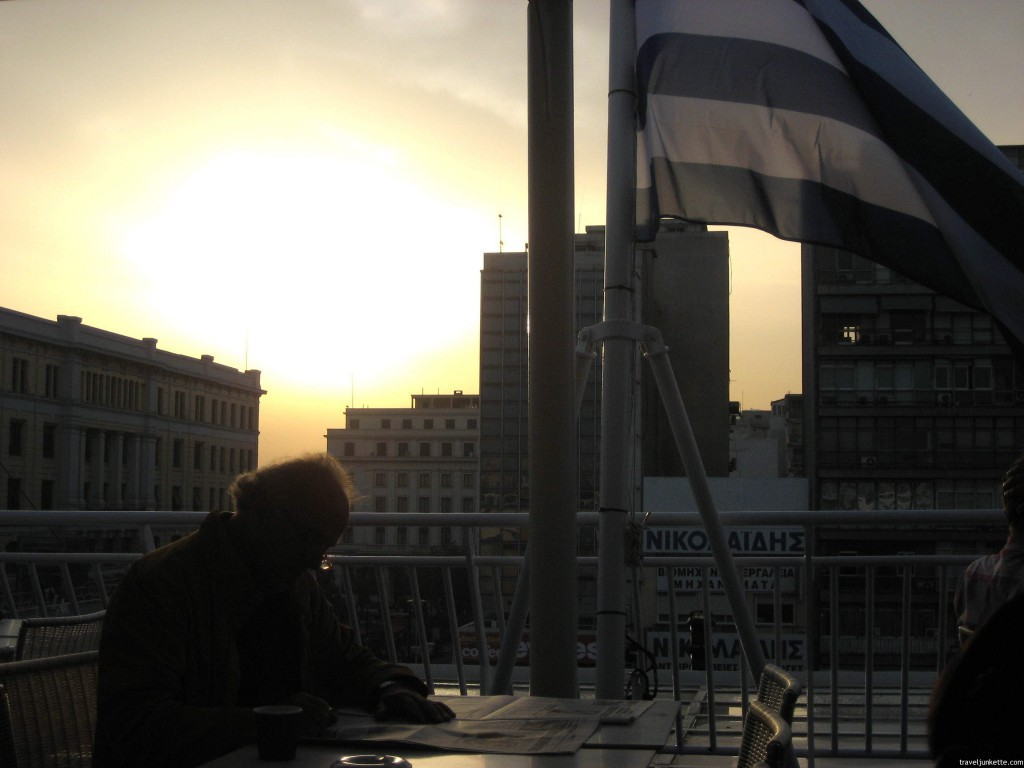 Man reading on Greek ferry at sunrise