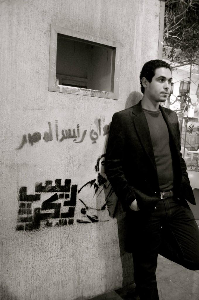 Man standing next to graffiti in Cairo