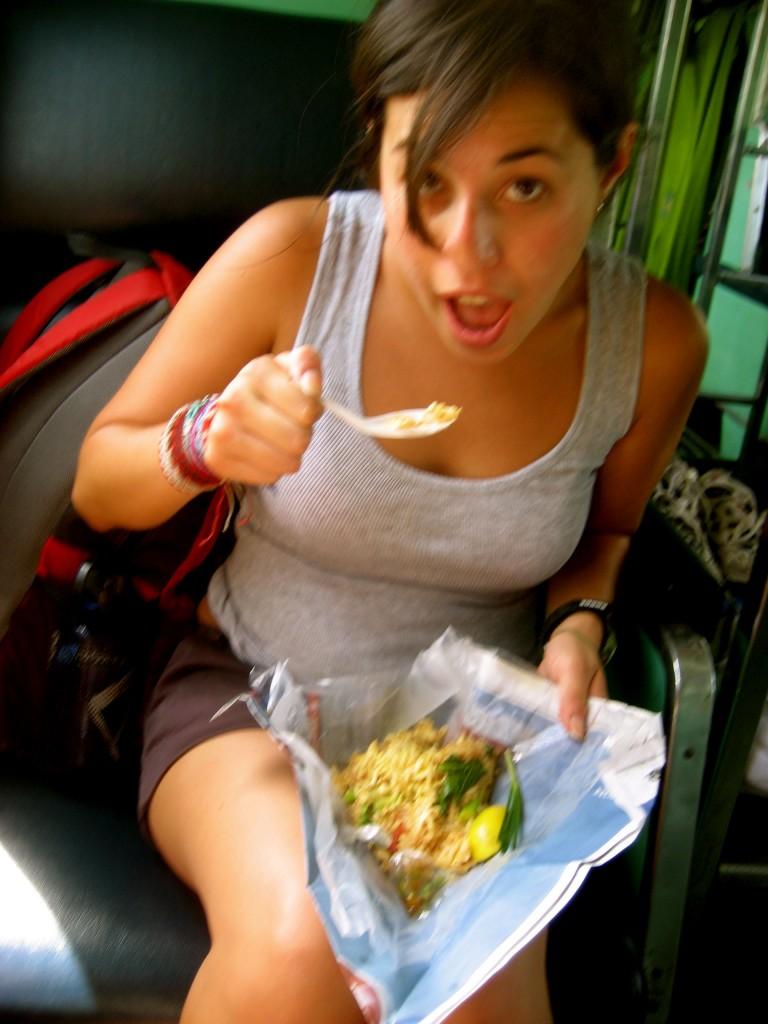 Girl eating Thai food from a banana leaf
